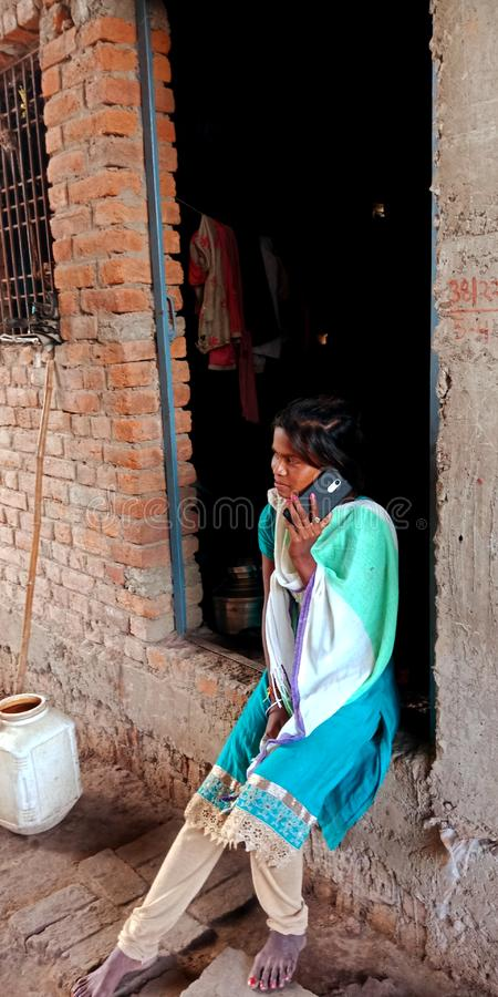 An indian village teen talking to mobile phone. Woman, operating, laptop, computer, system, seating, cot, students, school, studying, classroom, farmer, forest royalty free stock image