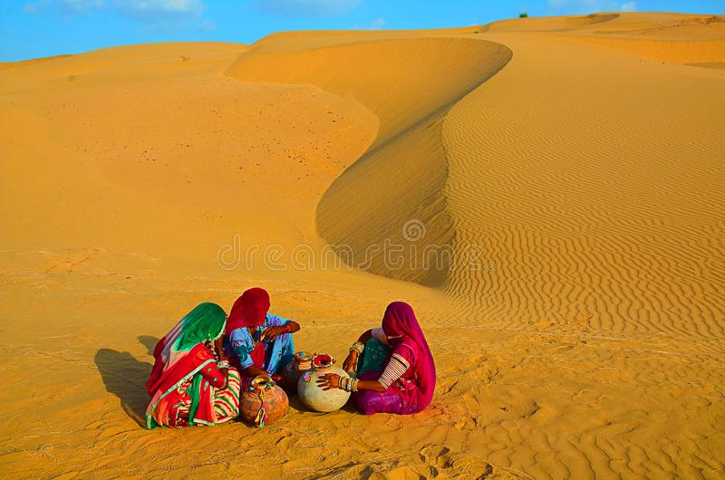 Indian village women sitting on in desert wearing ethnic traditional outfits with water jugs water crises, jaisalmer, rajasthan, royalty free stock photos