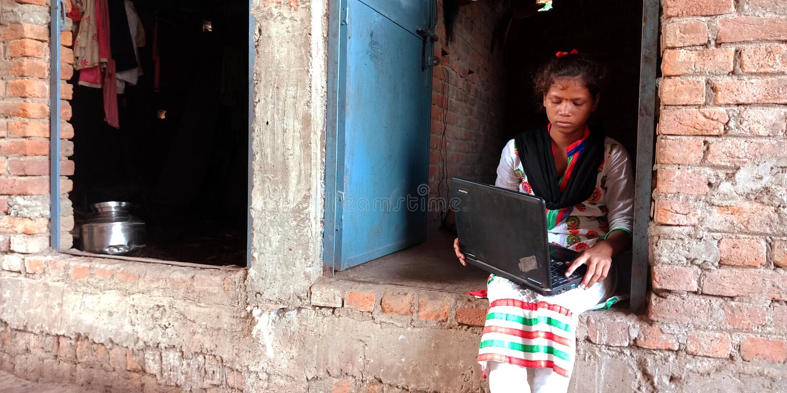 An indian villager teen operating laptop computer seating at corridor. Grandfather, using, mobile, conversation, matured, learning, system, illiterate, people stock images