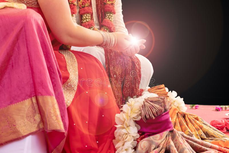 Indian wedding ceremony, bride and groom holding fire in hands on black background with copy space.  royalty free stock photo