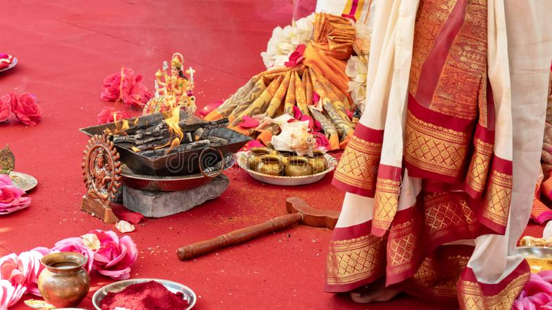 Indian wedding ceremony, decorations for traditional ethnic rituals for marriage, fire burning, flowers and statuettes of the. Deity on red carpet stock photo