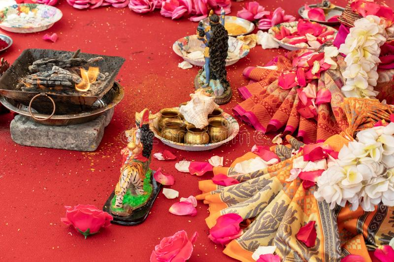 Indian wedding ceremony, decorations for traditional ethnic rituals for marriage, fire burning, flowers and statuettes of the. Deity on red carpet royalty free stock image