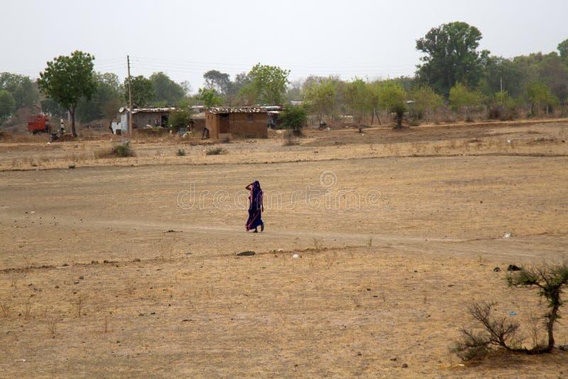 Indian woman in a blue dress walks through a village Maidan stock photos