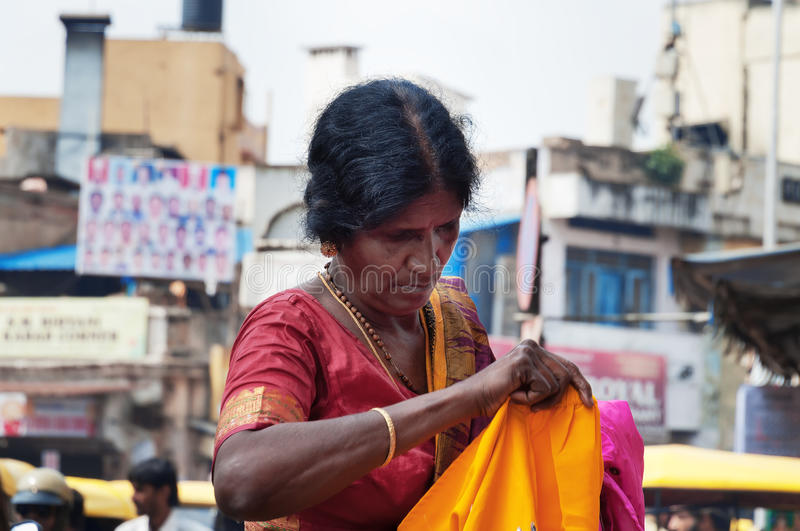 Indian woman chooses clothes at the Russell market in Bangalore. BANGALORE, INDIA - DEC 25, 2014: Unidentified Indian woman chooses clothes at the Russell market royalty free stock photography