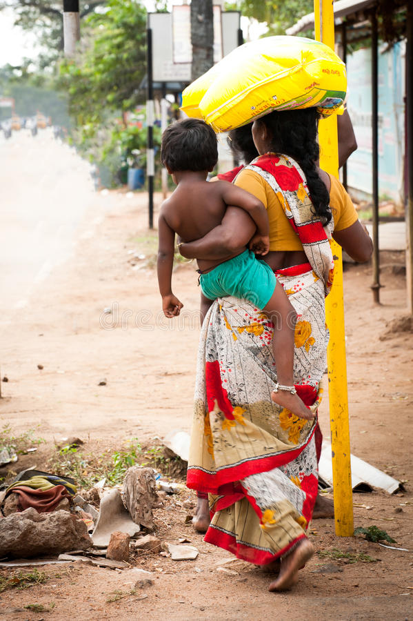 Indian woman in colorful sari with baby carrying bale on head stock photos