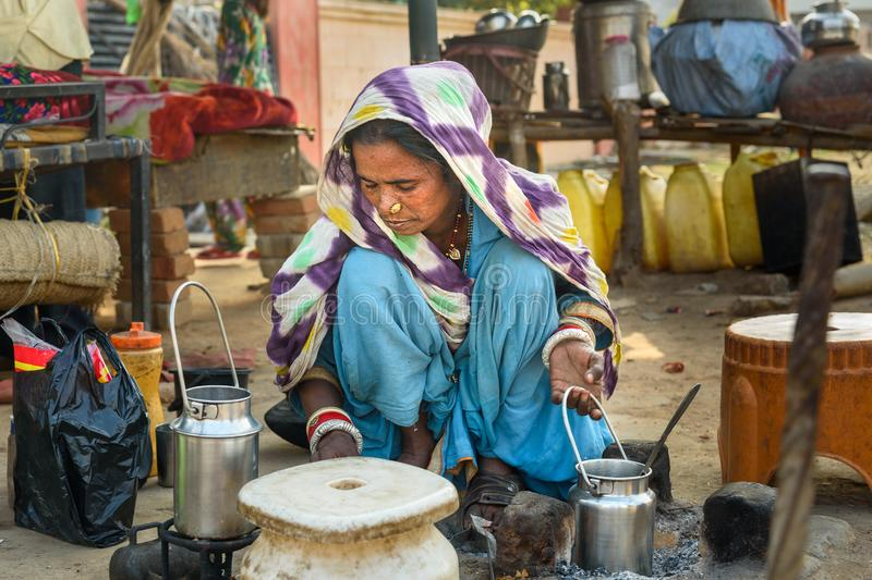 Indian woman cooking on the street. Poor people come with family to the city from the village for work. And they living in the. Ajmer, India - February 07, 2019 royalty free stock photos