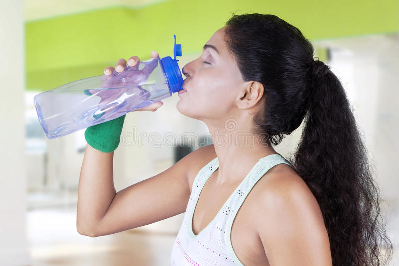 Indian woman drinks water in fitness center stock photos