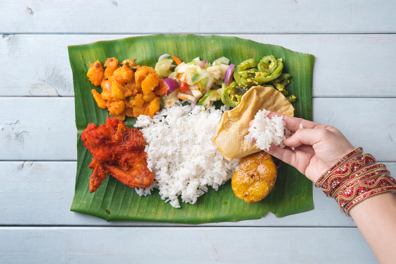 Indian woman eating banana leaf rice. Overhead view on wooden dining table stock images