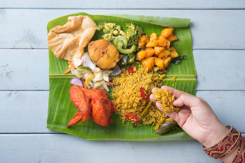 Indian woman eating biryani banana leaf rice. Overhead view of Indian woman eating biryani banana leaf rice on wooden dining table stock photography