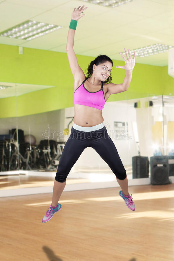 Indian woman jumping at gym. Joyful indian woman celebrate her weight loss success and jumping in the fitness center with sportswear stock image