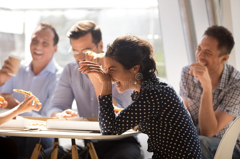 Indian woman laughing eating pizza with diverse coworkers in off stock photos