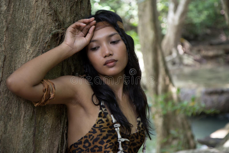 Indian woman. Leaning against a tree stock image