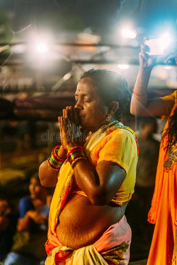 Indian woman praying on the boat in the area of Varanasi Ganga Aarti at holy Dasaswamedh Ghat, near Kashi Vishwanath Temple. Indian woman praying on the boat in royalty free stock images