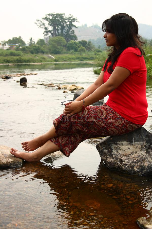 Download Indian Woman In Red Dress Sitting On A Rock Stock Photo - Image of attractive, indian: 18779144