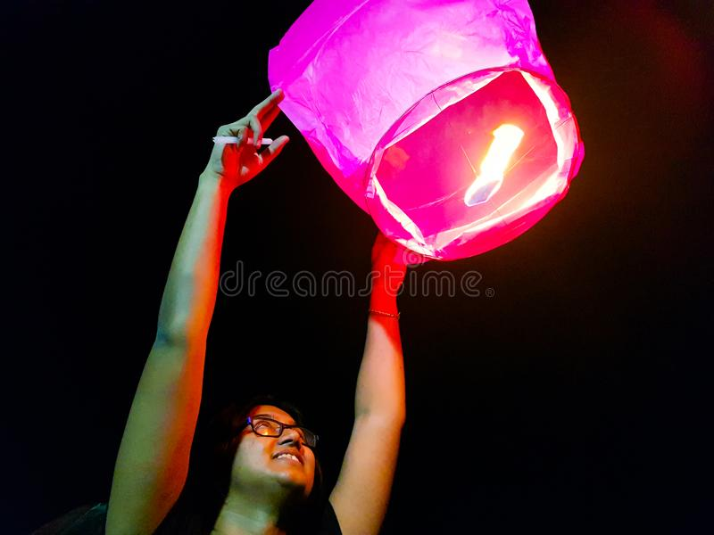An indian woman releasing a lighted paper hot air balloon in sky lantern festival.  stock images