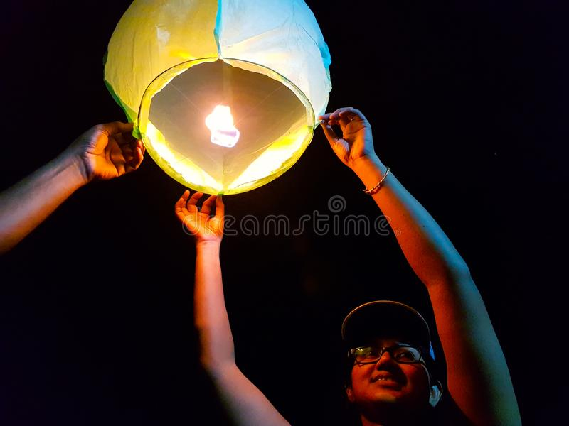 An indian woman releasing a lighted paper hot air balloon in sky lantern festival.  stock photos