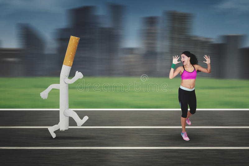 Indian woman running away from a cigarette. Portrait of Indian woman wearing sportswear while running away from a cigarette with a fast motion blur background stock photo