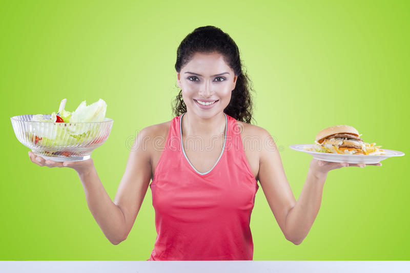 Indian woman with salad and hamburger. Portrait of beautiful indian woman holding a bowl of fresh salad and hamburger with green background stock photos