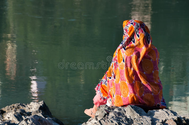 Indian woman in sari sits on a rock at the River Ganga. RISHIKESH, INDIA - DEC 10, 2014: Unidentified Indian woman in sari sits on a rock at the River Ganga royalty free stock images