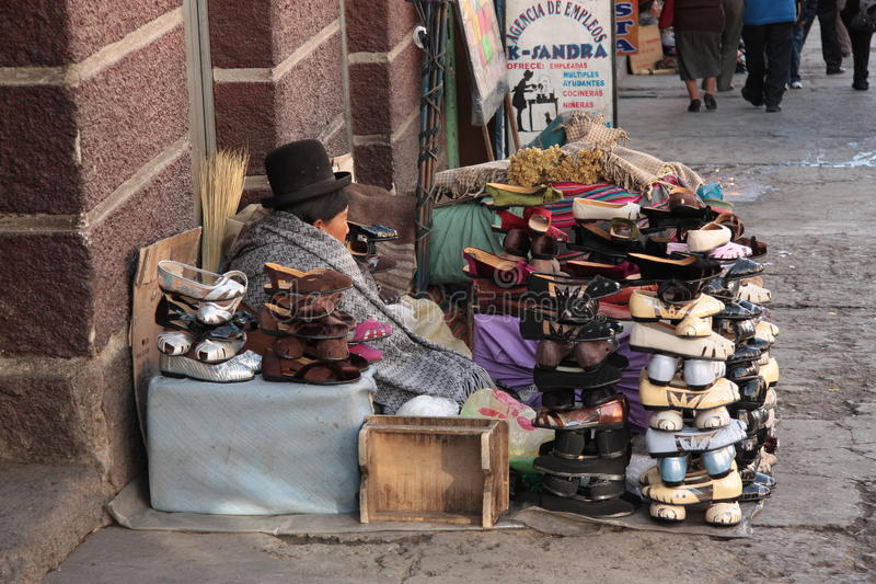 Indian woman sells shoes in street, La Paz, Bolivia. Indian Aymara woman sells traditional cholita style shoes in a street of La Paz, Bolivia, South America royalty free stock photo
