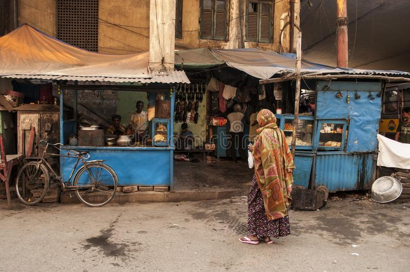 Indian woman stands by streets shops in Kolkata. royalty free stock photography