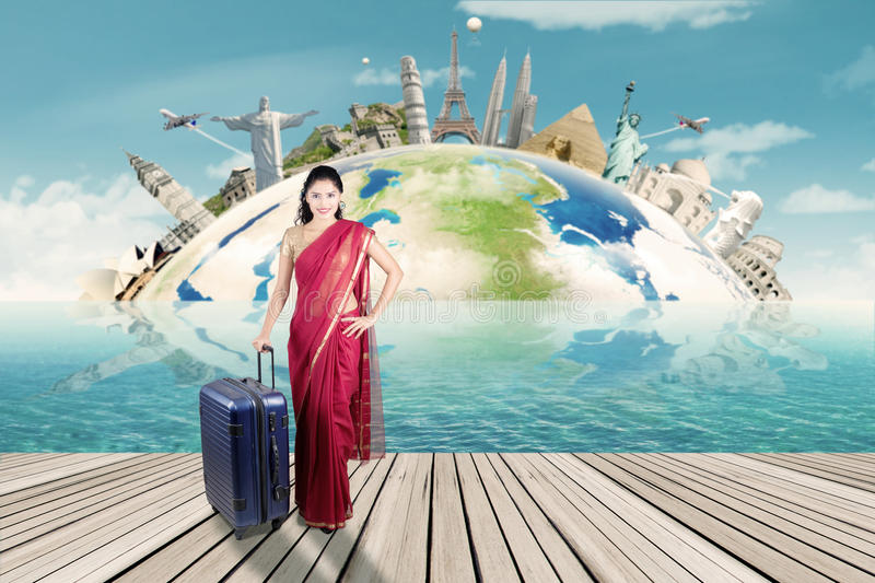 Indian woman with suitcase and map of world monument royalty free stock photography