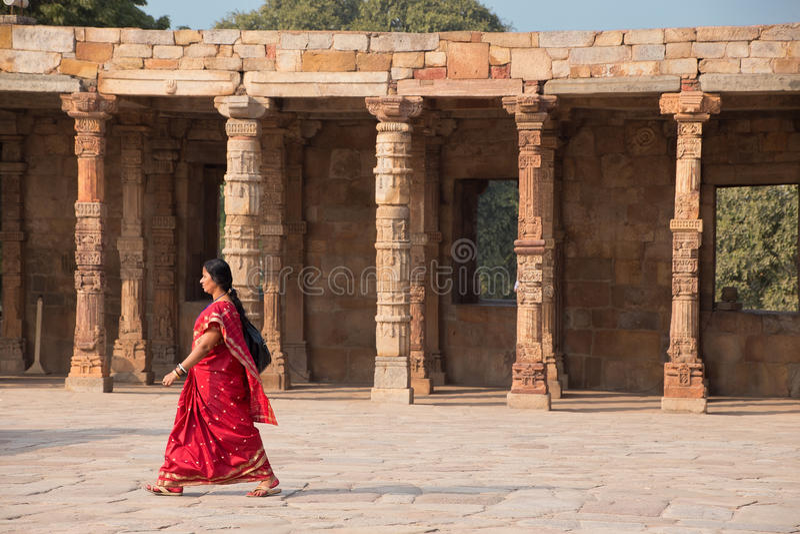 Indian woman walking through courtyard of Quwwat-Ul-Islam mosque royalty free stock photos