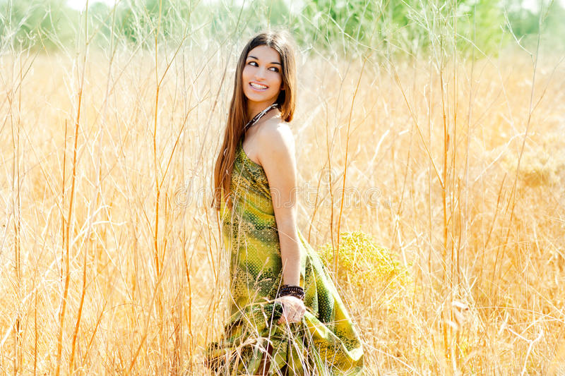 Indian woman walking outdoors in golden field stock photography