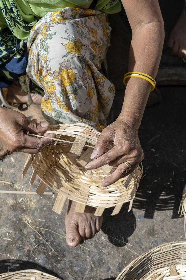Indian woman weaves a bamboo basket with her legs and arms in an market, close up. India. Indian woman weaves a bamboo basket with her legs and arms in an local royalty free stock photo
