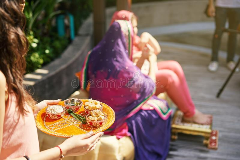 Indian women holding tray with prayer items with indian bride in blurry background stock photography