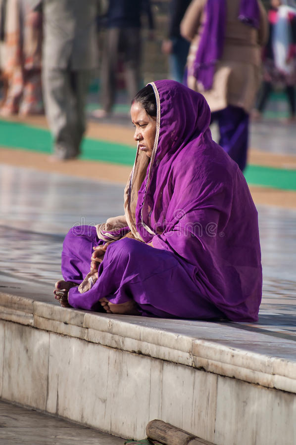 Indian women in purple sari sitting near the lake at Golden Temple. Amritsar. India. AMRITSAR, INDIA, DEC - 7, 2014: Unidentified Indian women in purple sari stock photo