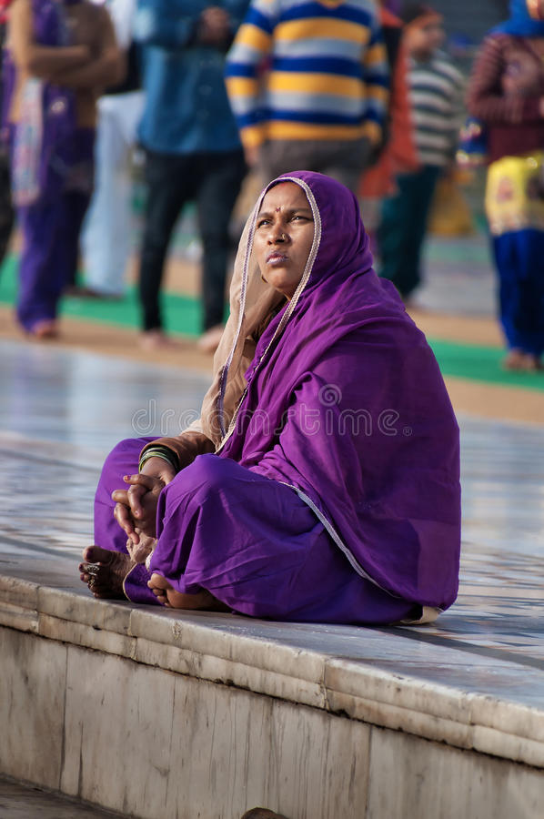 Indian women in purple sari sitting near the lake at Golden Temple. Amritsar. India. AMRITSAR, INDIA, DEC - 7, 2014: Unidentified Indian women in purple sari royalty free stock photos