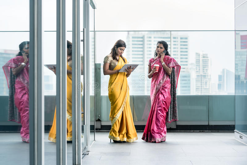 Indian women using modern technology for communication during th. Two young Indian women using modern technology for communication during the break at work in a stock images