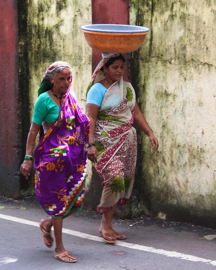 Indian women on the walk. In Mumbai of India,Dressed in traditional costumes lisa of India.The top of head is worn things stock photos