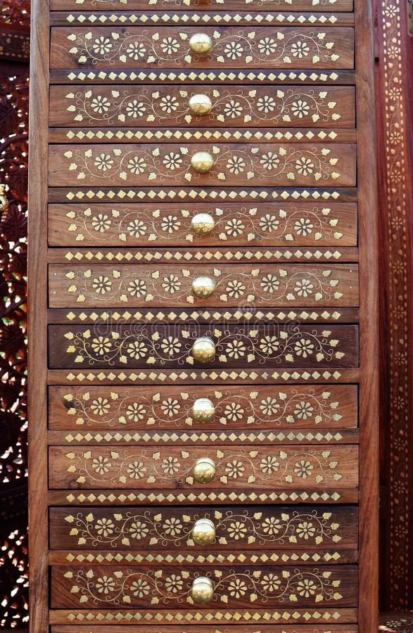 Indian wooden cabinet with drawers with golden inlay and round handles stock image