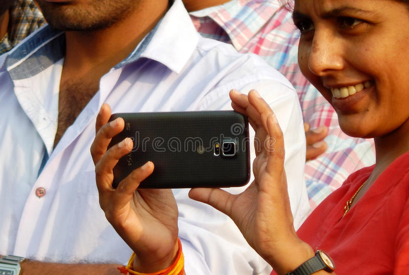 Indian young adult shoots an event with mobile phone royalty free stock photos