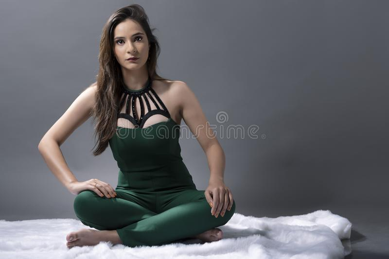 Indian young lady in green jump suit. In seated pose royalty free stock images