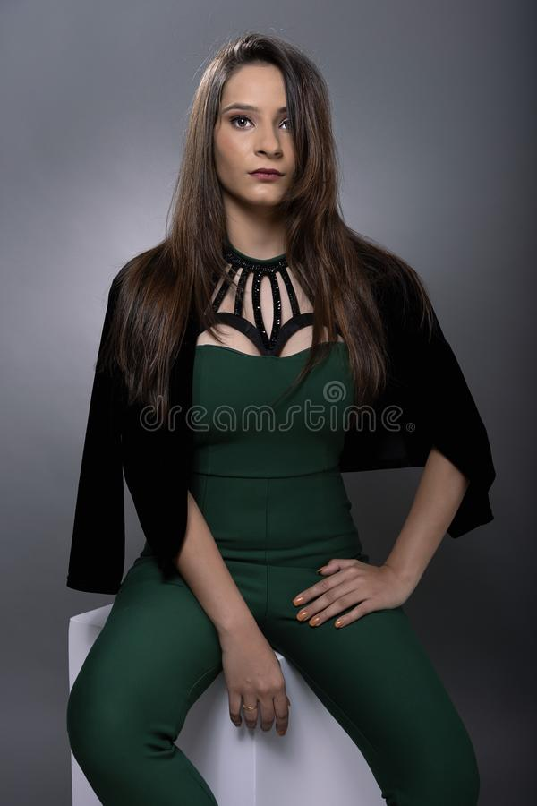 Indian young lady in green jump suit. In seated pose and jacket on shoulder stock photos