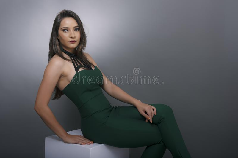 Indian young lady in green jump suit. In seated pose and jacket on shoulder royalty free stock image