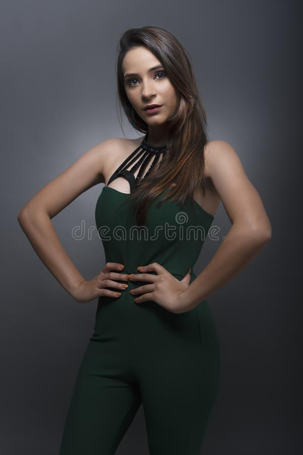 Indian young lady in green jump suit. In standing pose looking at camera stock photos