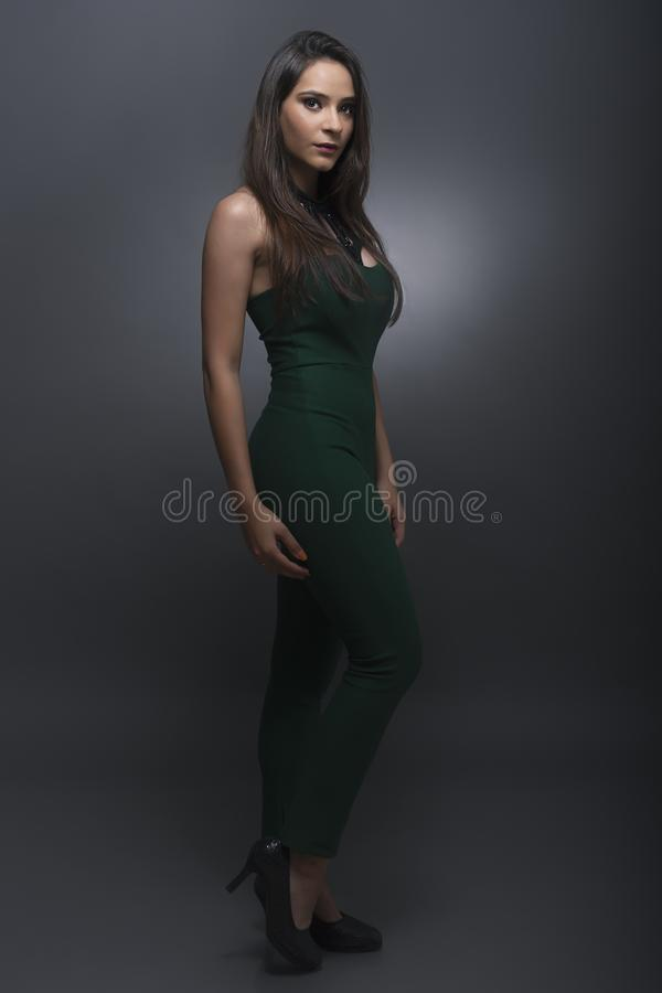 Indian young lady in green jump suit. In standing pose looking at camera stock image