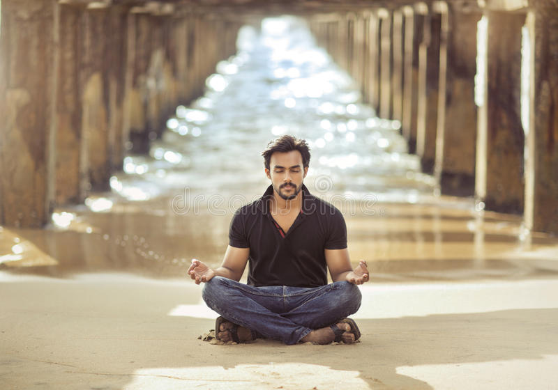 Indian young man meditating under the broken bridge royalty free stock photo