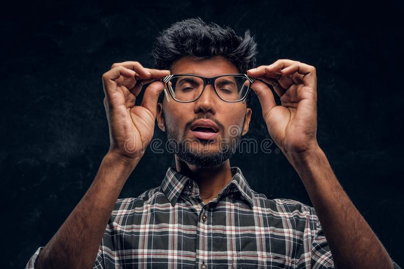 Indian young scholar in altered minds holding glasses and closing his eyes. Studio photo against a dark textured wall stock images