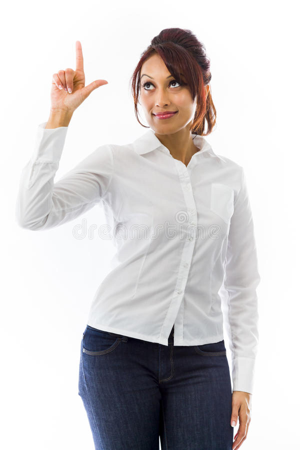 Indian young woman pointing upwards and looking at tip of finger. Adult indian woman in studio isolated on white background royalty free stock image