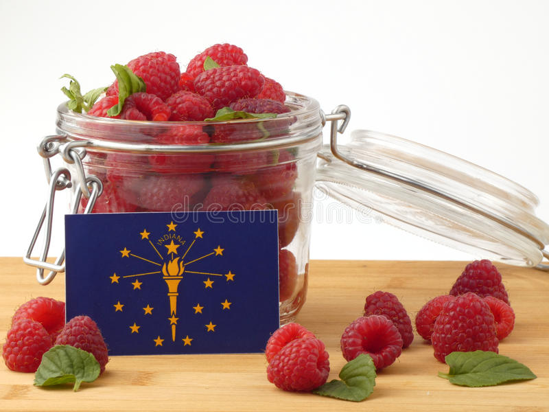 Indiana flag on a wooden panel with raspberries isolated on a wh stock photo