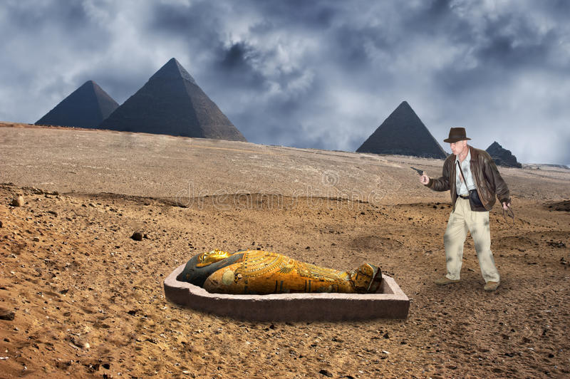 Indiana Jones Style Action Hero and Adventure. An Indiana Jones action hero character style shows our adventurer in the desert by the Great Pyramids of Egypt in royalty free stock photos