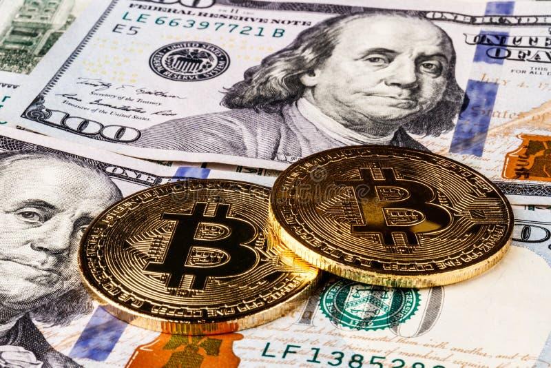 Indianapolis - circa abril de 2018: Bitcoin en una cama de cientos billetes de dólar Bitcoin se contrapesa para ser el Cryptocurr imagen de archivo