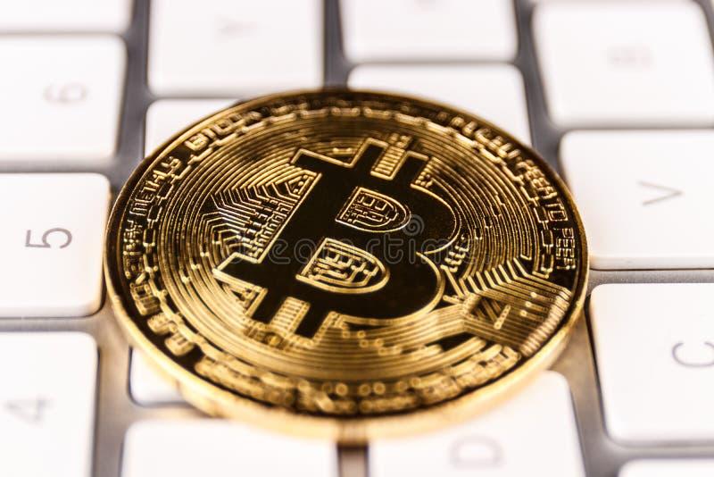 Indianapolis - Circa April 2018: Fysiska Bitcoin på ett datortangentbord Bitcoin är Cryptocurrency VII royaltyfri bild