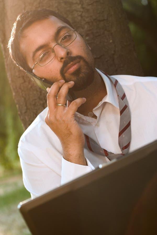 Indiano con il cellulare ed il computer portatile immagine stock libera da diritti