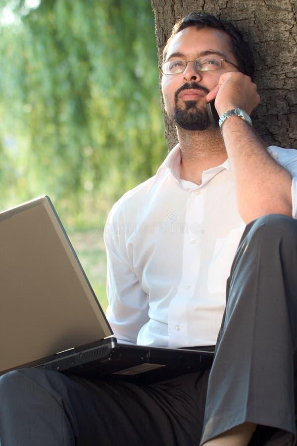 Indiano con il telefono mobile ed il computer portatile fotografie stock libere da diritti